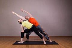 Paare führen Reihen der ausgedehnten Seitenwinkel-Yogapartnerhaltung durch Lizenzfreie Stockfotografie