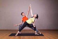 Paare führen Reihen der ausgedehnten Seitenwinkel-Yogapartnerhaltung durch Stockfotografie