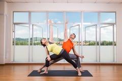 Paare führen Reihen der ausgedehnten Seitenwinkel-Yogapartnerhaltung durch Stockfotos