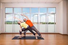 Paare führen Reihen der ausgedehnten Seitenwinkel-Yogapartnerhaltung durch Stockbilder