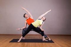 Paare führen Reihen der ausgedehnten Seitenwinkel-Yogapartnerhaltung durch Stockbild
