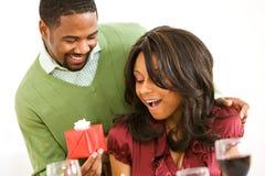 Paare: Frau überrascht durch Geschenk am Abendessen Lizenzfreie Stockfotos