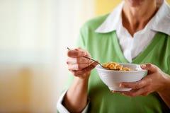 Paare: Frau, die Schüssel Getreide isst Stockbild