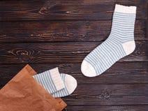 Paare Frauen ` s streiften Socken whith eine Papiertüte auf einem hölzernen Hintergrund Lizenzfreie Stockbilder