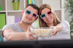 Paare genießen im Film und Zusammenhaltenpopcorn Stockbild