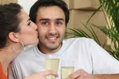 Paare gesessen durch gepackte Kästen Lizenzfreie Stockfotografie