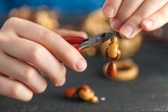 Paare Hände und Zangen, die eine Perlenhalskette zusammenbauen Stockfotografie