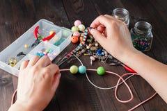 Paare Hände und Zangen, die eine Perlenhalskette zusammenbauen Lizenzfreies Stockfoto