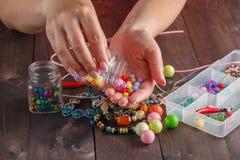 Paare Hände und Zangen, die eine Perlenhalskette zusammenbauen Lizenzfreie Stockbilder