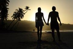 Paare Hand in Hand durch Sonnenuntergang Lizenzfreie Stockbilder