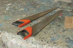 Paare Handsaws auf schmutzigem Boden mit blauer Farbe Lizenzfreies Stockbild