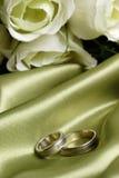 Paare Hochzeitsbänder auf grünem Satin lizenzfreie stockfotografie