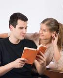 Paare im Büro, das ein Buch liest lizenzfreie stockbilder