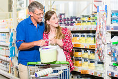 Paare im Baumarkt, der über Farbe der Farbe für renova argumentiert Lizenzfreies Stockbild