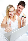 Paare im Bett, das online mit dem Daumen oben kauft Lizenzfreies Stockbild