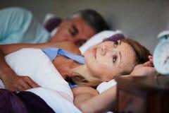 Paare im Bett mit der Frau, die unter Schlaflosigkeit leidet Stockfotografie