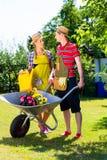 Paare im Garten mit Gießkanne Lizenzfreie Stockfotografie