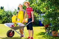 Paare im Garten mit Gießkanne Lizenzfreies Stockbild