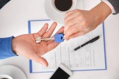 Paare im Immobilienverkaufsbüro mit dem Mittel, das Schlüssel Draufsicht führt lizenzfreie stockbilder
