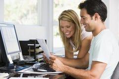 Paare im Innenministerium mit Computer und Schreibarbeit Lizenzfreies Stockfoto
