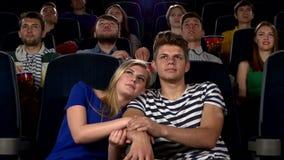 Paare im Kino, das einen Film aufpasst, und Küssen stock video footage