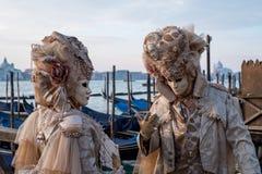 Paare im Kostüm und Masken, die mit zurück zu Grand Canal, San Giorgio im Hintergrund, während Venedig-Karnevals stehen lizenzfreie stockfotos