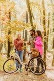 Paare im Liebesfahrfahrrad zusammen in Forest Park Freunde mit Fahrrad Bärtiger Mann und Frauen, die im Herbst sich entspannen stockfoto