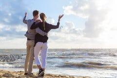 Paare im romantischen Sonnenuntergang auf Ozeanstrand Stockbild