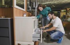 Paare im Schläger- und Möbelspeicher, der nach seins wählt und sucht Stockfoto