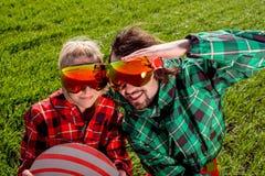 Paare im Skianzug und den Sonnenbrillen haben einen lustigen Blick zu kamen Stockfotografie