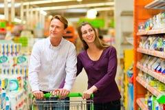 Paare im Supermarkt mit Einkaufswagen Stockbilder