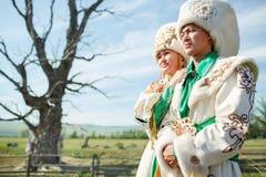 Paare im Trachtenkleid, auf epischem altem Baum des Hintergrundes an der Mitte der ländlichen Landschaft lizenzfreies stockbild