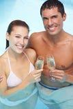Paare im trinkenden Funkeln des Pools Lizenzfreie Stockfotos