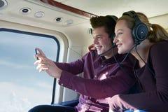 Paare im Urlaub, die Fahrt im Hubschrauber nehmen Stockfoto