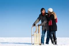 Paare im Winter mit Schlitten Lizenzfreie Stockfotografie
