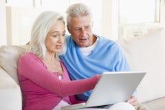 Paare im Wohnzimmer mit dem Laptoplächeln lizenzfreie stockfotografie