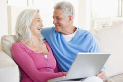 Paare im Wohnzimmer mit dem Laptoplächeln Lizenzfreie Stockbilder
