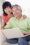 Paare im Wohnzimmer mit dem Laptoplächeln Lizenzfreies Stockfoto