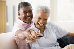 Paare im Wohnzimmer unter Verwendung des Fernsteuerungslächelns Stockbilder