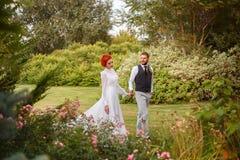 Paare Liebhaber, die in einen bunten Garten gehen Stockbilder