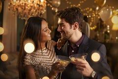 Paare machen Toast an der Kamera, während sie an der Partei feiern Stockfoto