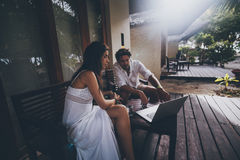 Paare: Mann und Frau mit Laptop auf Veranda Stockfoto
