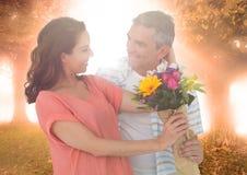 Paare mit Blumen gegen Bäume und Aufflackern Lizenzfreies Stockfoto