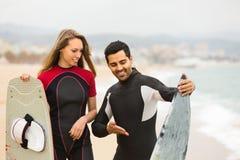 Paare mit Brandungsbrettern auf dem Strand Lizenzfreies Stockfoto