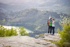 Paare mit dem Baby, das auf Klippe und dem Küssen steht stockbild