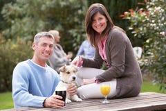 Paare mit dem Haustier-Hund, der draußen Getränk im Pub genießt stockfotografie