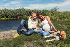 Paare mit dem Hund, der in einem Park sitzt Lizenzfreie Stockfotografie