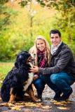 Paare mit dem Hund, der Herbst in der Natur genießt Stockbilder