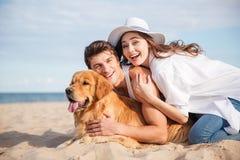 Paare mit dem Hund, der Spaß auf dem Strand lacht und hat Lizenzfreies Stockfoto