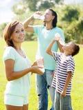 Paare mit dem Jugendlichkind, das von den Flaschen trinkt Lizenzfreie Stockfotos